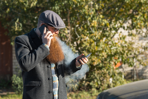 photo - dude vapes on his cell phone